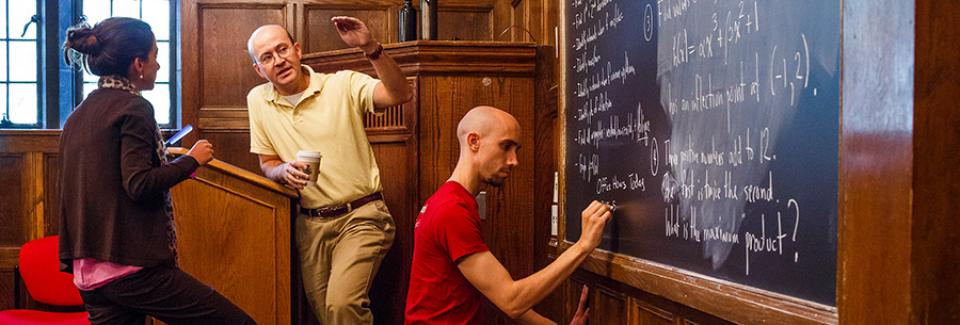 student writes on chalkboard while teacher and student talk at podium