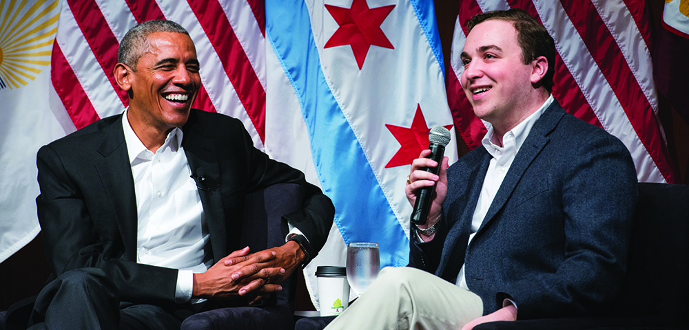 President Obama smiling on stage with a student