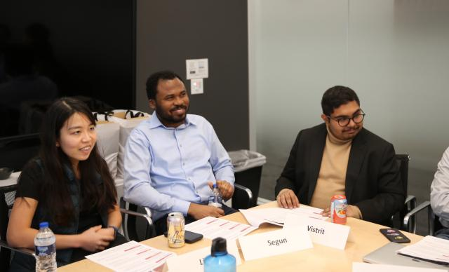The teammates Linh Dinh, Segun Fatidumu, and Vistrit Choudhary sit together at a table to share their work.