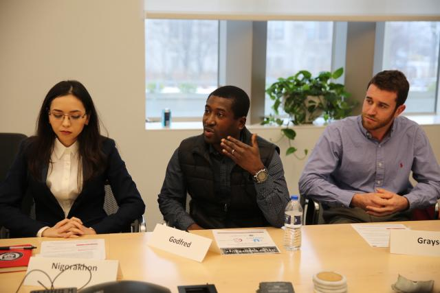 A table, with Kofi presenting his project with Grayson, seated to the left of him.