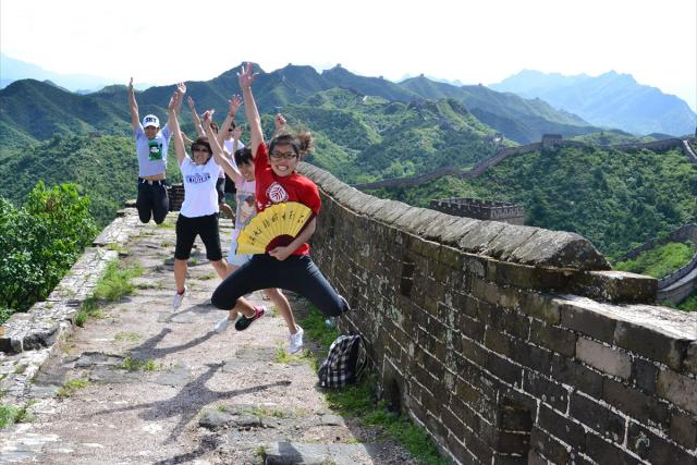 Students at the Great Wall jumping up with their hands up