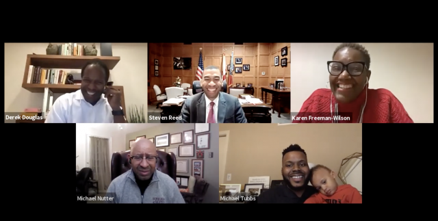 A screenshot of a panel discussion with several mayors and a small child.