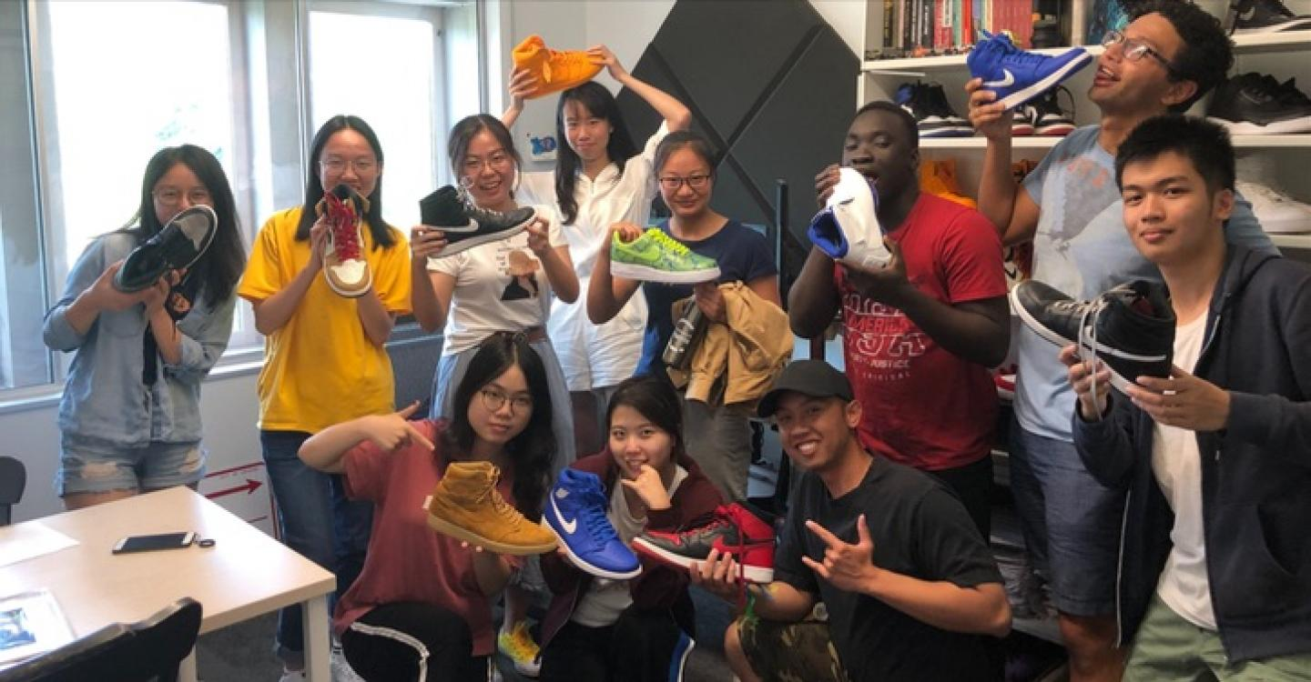 A group of 2019 DPSS students pose with Faculty Director Austin Wright's sneaker collection.