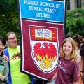 students hold a Harris School banner