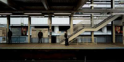 A photo of the outbound elevated platform of the Clark and Lake CTA station in Chicago. There are a few people on the platform. Photo by KE ATLAS on Unsplash